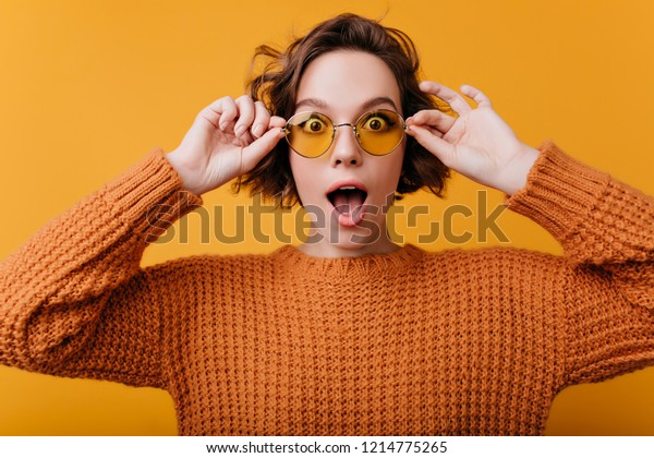 Close-up portrait of gorgeous white female model expressing amazement. Interested curly girl in knitted bright sweater touching her glasses.