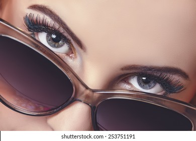 Closeup portrait of a gorgeous woman with beautiful bluish eyes giving a seductive hypnotic look over dark sunglasses.