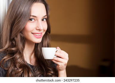 Closeup portrait of a gorgeous young brunette woman holding cup of coffee.