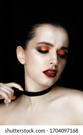 Close-up portrait of gorgeous young woman with red lips and bright makeup of eyes. Beautiful girl with a healthy clean skin against black background.