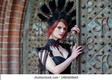 Closeup Portrait of Gothic Girl in Long Black Dress. Wearing Artistic Feather Crown with Roses. Posing Against Old Castle Gates. Horizontal Image Composition