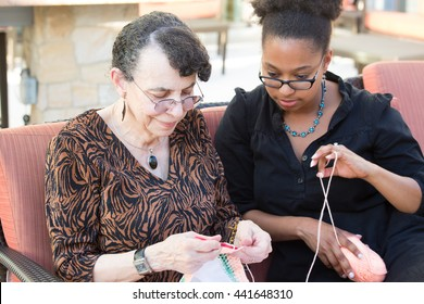 Closeup portrait, granddaughter and grandmother sitting, enjoying time together, isolated outdoors background