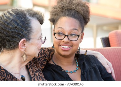 Closeup portrait, granddaughter and grandmother sitting, having deep conversation, looking at each other, isolated outdoors background