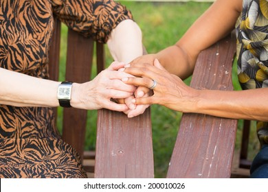 Closeup portrait of grandmother and daughter  holding hands, sitting down, isolated outdoors background