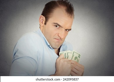 Closeup portrait greedy banker executive CEO boss, corporate employee funny looking man holding dollar banknotes scared to loose money, suspicious isolated grey background. Human face expression