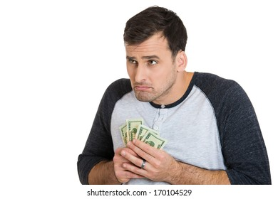 Closeup portrait of greedy man corporate employee, worker, student holding dollar banknotes tightly, isolated on white background. Negative human emotion facial expression feeling
