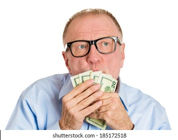 Closeup portrait, greedy senior executive, CEO, boss, old corporate employee, mature man, holding, kissing dollar banknotes in hand, isolated white background. Negative human emotion facial expression