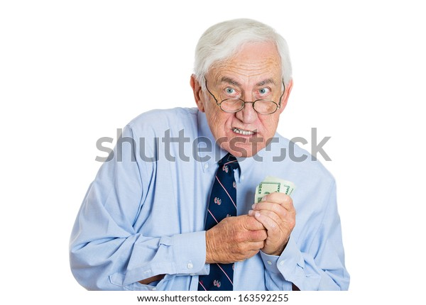 Closeup portrait of greedy senior executive, CEO, boss, old corporate employee, mature man, holding dollar banknotes tightly, isolated on white background. Negative human emotion facial expression