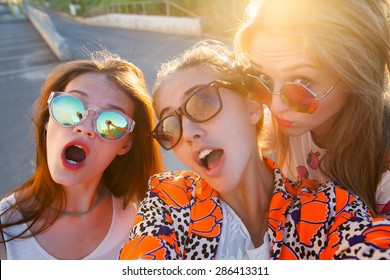 Close-up portrait of group of tree young friends wearing sunglasses,stylish friends,hugging and standing in a row at sunset, spending time with friends.posing on gold sunset,Make self picture