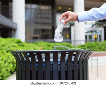 Closeup portrait, hand throwing plastic empty water bottle in recycling bin, isolated building and trees background