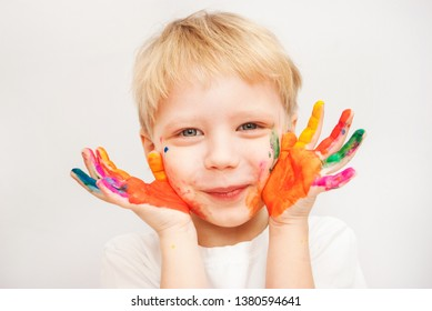 Closeup portrait of handsome 4 years age little boy looking at camera holding colorful painted hands near face smiling. Children art and creation concept. Horizontal color photography.