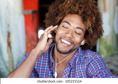 closeup portrait of a handsome African American man at the beach listening to music