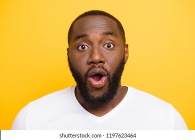 Close-up portrait of handsome attractive manly shocked guy in white t-shirt, opened mouth, isolated over bright vivid yellow background