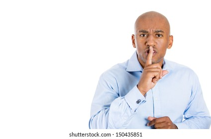 """Closeup portrait of handsome bald man placing finger on lips as if to say, """"shhhhh"""", """"be quiet"""", """"silence"""" , isolated on white background with copy space"""