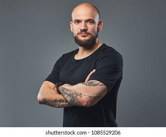 Close-up portrait of a handsome bearded athlete in a black t-shirt, posing with crossed arms in a studio.