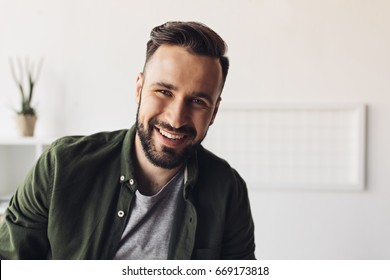 Close-up portrait of handsome bearded man smiling at camera