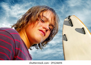 Closeup portrait of a handsome boy with surfboard