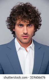 Closeup portrait of a handsome businessman with curly hair on gray background