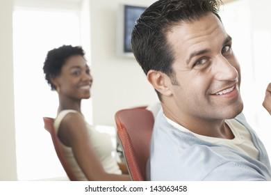 Closeup portrait of handsome businessman with female colleague in background
