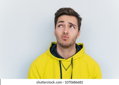 Closeup portrait of handsome Caucasian male curves lips, looks up doubtfully, wearing stylish yellow hoodie, thinks what to do. Pensive man posing over white background in studio. Copy space