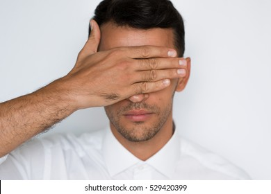 Close-up portrait of a handsome caucasian man cover eyes with hand isolated on gray background. Attractive businessman blindfolded protection.