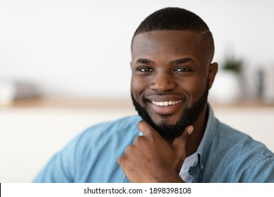 Closeup portrait of handsome cheerful african american man touching beard. Confident black millennial guy looking at camera and smiling, selective focus with copy space