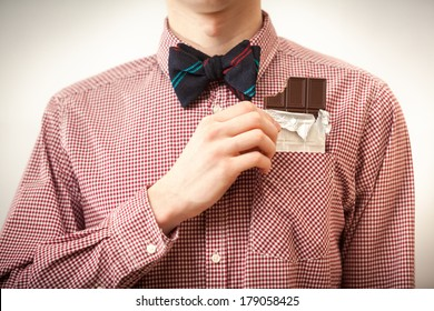 Closeup portrait of handsome hipster man in shirt and bow tie taking chocolate out of breast-pocket