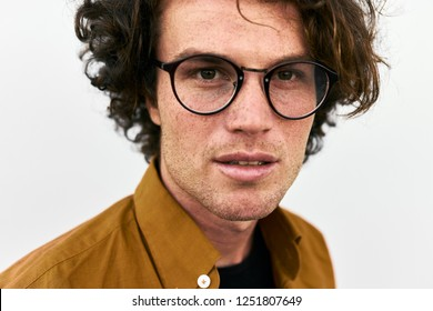 Closeup portrait of handsome man posing for advertisement wears round glasses, looking to the camera, isolated on white wall outdoor. Portrait of smart student male. People emotion concept