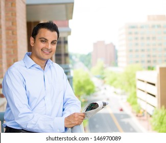 Closeup portrait of handsome man reading newspaper on his outside balcony isolated on a city background with trees, buildings and cars