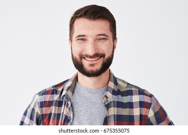 Close-up portrait of a handsome man with a smile on his face. Fashion portrait of an attractive young bearded man in the studio