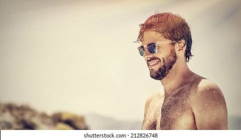 Closeup portrait of handsome man wearing stylish sunglasses, fashionable attractive model on the beach, summer vacation, freedom and pleasure concept