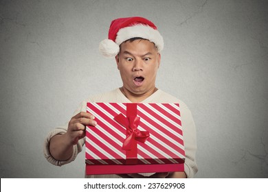 Closeup portrait handsome middle aged man wearing red santa claus hat opening gift box surprised happy at what he gets isolated grey wall background. Positive human emotion facial expression feeling