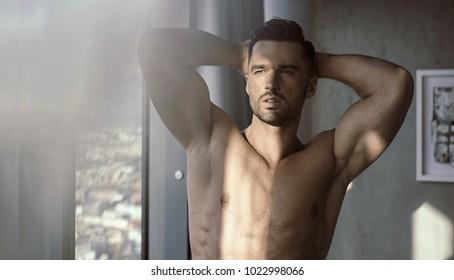 Closeup portrait of a handsome, muscular guy in bedroom