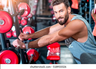 Close-up portrait of handsome muscular man standing in the gym with red dumbbells on the background