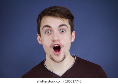 Closeup portrait handsome, startled, surprised, shocked, stunned young man, in full disbelief, isolated, dark blue background. Human face expressions, emotions, reaction, perception