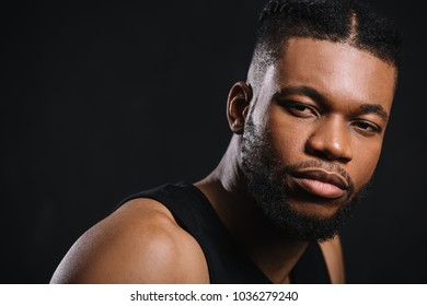 close-up portrait of handsome young athletic african american man looking at camera isolated on black