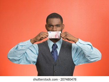 Closeup portrait handsome young corrupt corporate man in blue shirt holding euro bill currency to his mouth, isolated red background. Bribery concept in politics, business, diplomacy. Life perception
