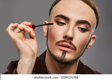 Closeup portrait of handsome young man, visagist or male makeup artist,  applying mascara, wearing gold eyeshadow, anchor beard and mustache, looking aside while holding mascara brush close to face.