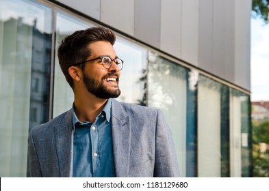 Closeup portrait Handsome young man in front of modern office smiling and looking in the distance