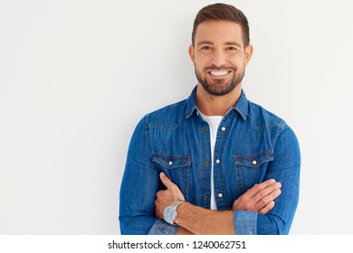 Close-up portrait of handsome young man looking at camera and smiling while wearing casual clothes and standing at isolated white background.
