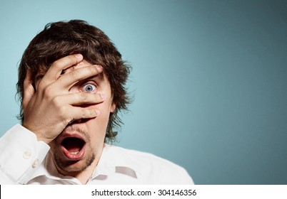 Closeup portrait of handsome young man looking shocked, surprised in disbelief, with hands on face looking at you camera, isolated on background. Positive human emotions, facial expressions