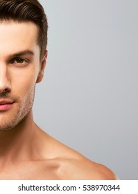 Closeup portrait of a handsome young man over grey background. Half face.