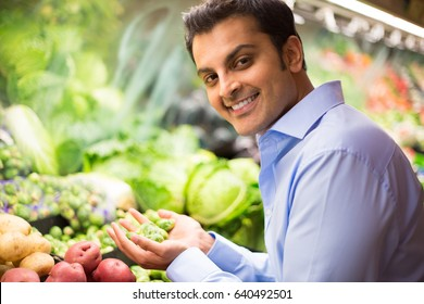Closeup portrait, handsome young man in blue shirt picking up green brussel sprouts, choosing vegetables in grocery store