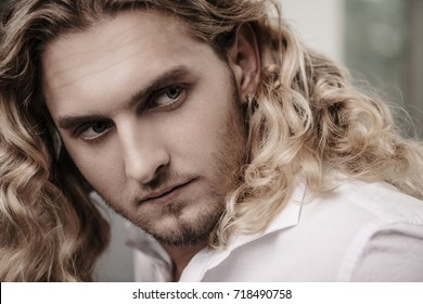 Close-up portrait of a handsome young man with long curly blond hair. Men's beauty, health. Skincare, cosmetics.