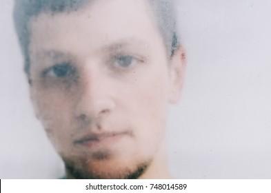 Closeup portrait of handsome young man looking through wet window