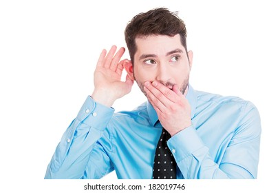 Closeup portrait of handsome, young, nosy man trying to secretly listen in on conversation, hand to mouth, surprised excited, juicy gossip he is hearing, privacy violation isolated on white background