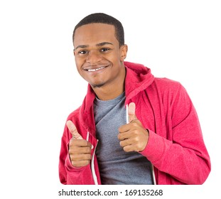 Closeup portrait of handsome young smiling man in black hoodie giving two thumbs up sign at camera isolated on white background. Positive human emotions facial expression feelings. Symbols