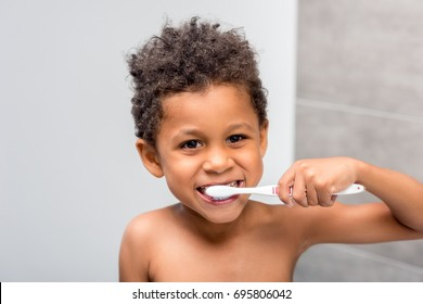 close-up portrait of happy african-american kid brushing teeth