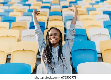 Close-up portrait of the happy afro-american woman cheerfing for the team on the stadium.