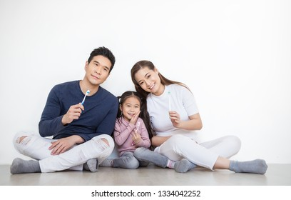 Closeup portrait of happy asian family hold toothbrushes smiling isolated on white. Asian father mother daughter little toddler girl brushing tooth, healthcare hygiene strong family together concept